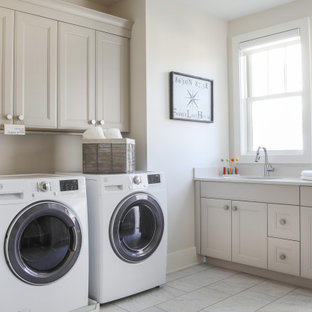 Utility room - mid-sized transitional l-shaped porcelain tile and gray floor utility room idea in Milwaukee with an undermount sink, recessed-panel cabinets, a side-by-side washer/dryer, beige cabinets, beige walls and white countertops