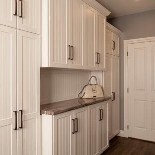 Exempel på ett stort klassiskt beige linjärt beige grovkök, med en dubbel diskho, luckor med lamellpanel, beige skåp, laminatbänkskiva, grå väggar, mörkt trägolv, en tvättmaskin och torktumlare bredvid varandra och brunt golv