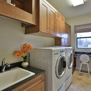 Immagine di una lavanderia bohémian con lavello da incasso, ante con riquadro incassato, ante in legno scuro, top in granito, pareti beige, pavimento con piastrelle in ceramica e lavatrice e asciugatrice affiancate