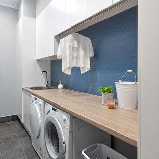 Inspiration för en liten funkis oranga linjär oranget tvättstuga enbart för tvätt, med en nedsänkt diskho, släta luckor, vita skåp, laminatbänkskiva, blå väggar, klinkergolv i porslin, en tvättmaskin och torktumlare bredvid varandra och grått golv