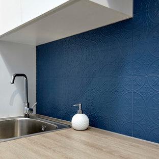 Idéer för att renovera en liten funkis oranga linjär oranget tvättstuga enbart för tvätt, med en nedsänkt diskho, släta luckor, vita skåp, laminatbänkskiva, blå väggar, klinkergolv i porslin, en tvättmaskin och torktumlare bredvid varandra och grått golv