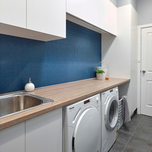 Small contemporary single-wall dedicated laundry room in Adelaide with a drop-in sink, flat-panel cabinets, white cabinets, laminate benchtops, blue walls, porcelain floors, a side-by-side washer and dryer, grey floor and orange benchtop.