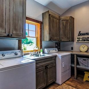 Idéer för en stor industriell l-formad tvättstuga enbart för tvätt, med en nedsänkt diskho, luckor med infälld panel, skåp i slitet trä, laminatbänkskiva, grå väggar, vinylgolv, en tvättmaskin och torktumlare bredvid varandra och brunt golv