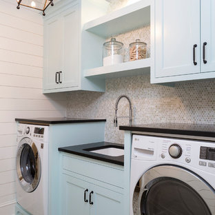 This is an example of a beach style single-wall separated utility room in Minneapolis with shaker cabinets, blue cabinets, a submerged sink, white walls, multi-coloured floors and black worktops.
