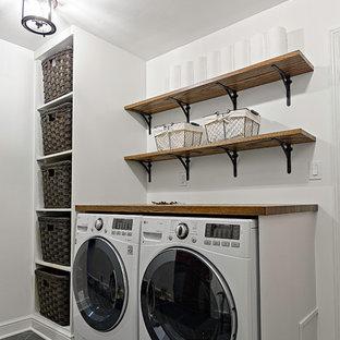 Foto di una lavanderia classica di medie dimensioni con ante con riquadro incassato, ante in legno bruno, top in granito e pavimento in legno massello medio