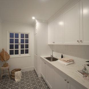 На фото: отдельная, параллельная прачечная в современном стиле с фасадами в стиле шейкер, белыми фасадами, мраморной столешницей, белым фартуком, фартуком из керамической плитки, полом из керамической плитки, со скрытой стиральной машиной, разноцветным полом и белой столешницей