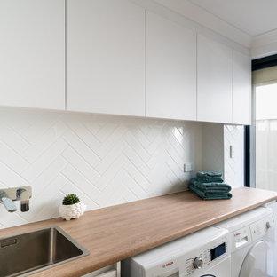 Inspiration för en liten funkis bruna parallell brunt tvättstuga enbart för tvätt, med en nedsänkt diskho, släta luckor, vita skåp, laminatbänkskiva, vitt stänkskydd, stänkskydd i keramik, vita väggar, klinkergolv i keramik, en tvättmaskin och torktumlare bredvid varandra och brunt golv