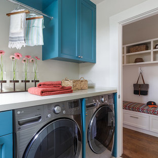 This is an example of a small country single-wall dedicated laundry room in San Francisco with blue cabinets, quartz benchtops, porcelain floors, a side-by-side washer and dryer, recessed-panel cabinets and grey walls.