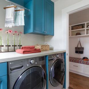 サンフランシスコの小さいカントリー風おしゃれな洗濯室 (青いキャビネット、クオーツストーンカウンター、磁器タイルの床、左右配置の洗濯機・乾燥機、落し込みパネル扉のキャビネット、グレーの壁) の写真