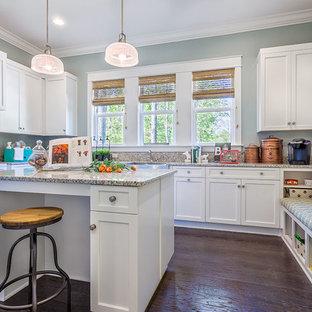Bild på ett mycket stort vintage u-format grovkök, med en rustik diskho, skåp i shakerstil, vita skåp, granitbänkskiva, blå väggar, mörkt trägolv, en tvättmaskin och torktumlare bredvid varandra och brunt golv