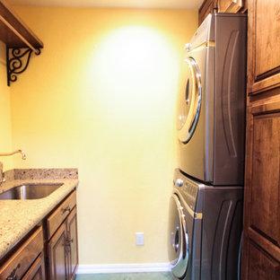 Inredning av en klassisk liten linjär tvättstuga enbart för tvätt, med en tvättpelare, en undermonterad diskho, skåp i shakerstil, skåp i mellenmörkt trä, granitbänkskiva, beige väggar, betonggolv och grönt golv