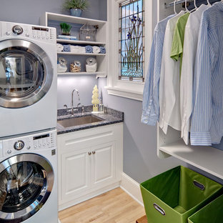 Photo of a small classic l-shaped separated utility room in Minneapolis with a stacked washer and dryer, white cabinets, a submerged sink, raised-panel cabinets, granite worktops, blue walls, light hardwood flooring, beige floors and grey worktops.