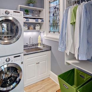 ミネアポリスの小さいL型トラディショナルスタイルの洗濯室の画像 (上下配置の洗濯機・乾燥機、白いキャビネット、アンダーカウンターシンク、レイズドパネル扉のキャビネット、御影石カウンター、青い壁、淡色無垢フローリング、ベージュの床、グレーのキッチンカウンター)
