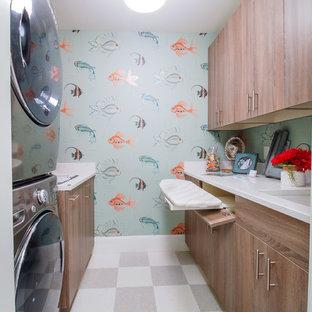 ミネアポリスの中サイズのビーチスタイルのおしゃれな洗濯室 (アンダーカウンターシンク、フラットパネル扉のキャビネット、大理石カウンター、青い壁、リノリウムの床、上下配置の洗濯機・乾燥機、中間色木目調キャビネット) の写真