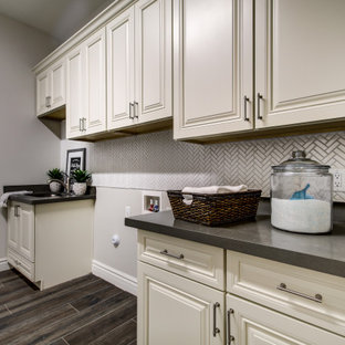 Design ideas for a large dedicated laundry room in Phoenix with an undermount sink, white cabinets, white splashback, beige walls, a side-by-side washer and dryer, brown floor, grey benchtop and vaulted.