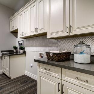 Inredning av en stor grå grått tvättstuga enbart för tvätt, med en undermonterad diskho, vita skåp, vitt stänkskydd, beige väggar, en tvättmaskin och torktumlare bredvid varandra och brunt golv