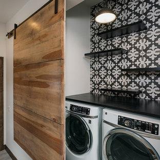 Idéer för att renovera en liten funkis svarta linjär svart liten tvättstuga, med öppna hyllor, svarta skåp, bänkskiva i kvarts, flerfärgade väggar, klinkergolv i keramik, en tvättmaskin och torktumlare bredvid varandra och svart golv