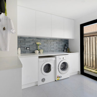 Photo of a contemporary l-shaped laundry room in Melbourne with flat-panel cabinets, white cabinets, grey floor and grey benchtop.