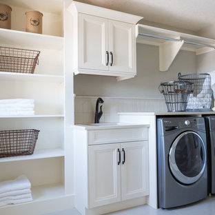 This is an example of a large traditional single-wall utility room in Calgary with a submerged sink, white cabinets, quartz worktops, porcelain flooring, a side by side washer and dryer, recessed-panel cabinets and grey walls.