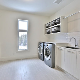 Large modern galley utility room in Toronto with a single-bowl sink, flat-panel cabinets, light wood cabinets, engineered stone countertops, white walls, light hardwood flooring and a side by side washer and dryer.