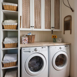 Photo of a country laundry room in Dallas with recessed-panel cabinets, white cabinets, beige walls, brick floors, a side-by-side washer and dryer, red floor and beige benchtop.