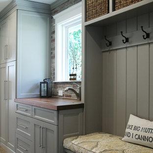 Идея дизайна: параллельная универсальная комната среднего размера в классическом стиле с хозяйственной раковиной, фасадами с утопленной филенкой, серыми фасадами, деревянной столешницей, серыми стенами, полом из керамогранита, со стиральной и сушильной машиной рядом, коричневым полом и разноцветной столешницей