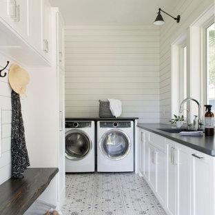 Inredning av en klassisk grå grått tvättstuga, med öppna hyllor, vita skåp, bänkskiva i kvarts, vita väggar, klinkergolv i keramik och en tvättmaskin och torktumlare bredvid varandra