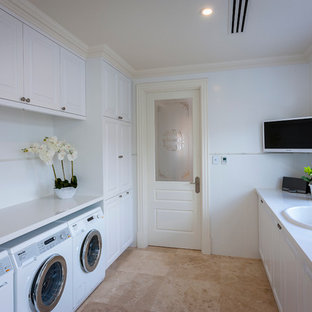 Large classic galley utility room in Perth with a built-in sink, shaker cabinets, white cabinets, white walls, a side by side washer and dryer, engineered stone countertops and travertine flooring.