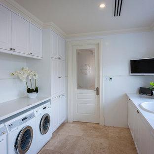 Ispirazione per una grande lavanderia multiuso classica con lavello da incasso, ante in stile shaker, ante bianche, pareti bianche, lavatrice e asciugatrice affiancate, top in quarzo composito e pavimento in travertino