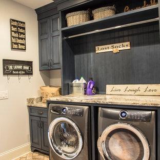 Foto di una sala lavanderia country di medie dimensioni con ante con bugna sagomata, ante blu, top in granito, pareti beige, pavimento in mattoni, lavatrice e asciugatrice affiancate, pavimento marrone e top marrone