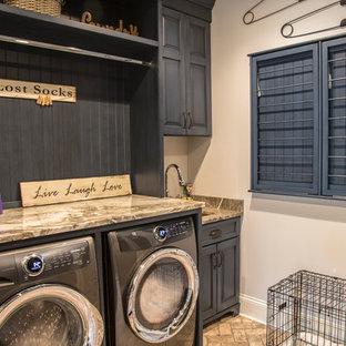 Immagine di una sala lavanderia country di medie dimensioni con ante con bugna sagomata, ante blu, top in granito, pareti beige, pavimento in mattoni, lavatrice e asciugatrice affiancate, pavimento marrone e top marrone