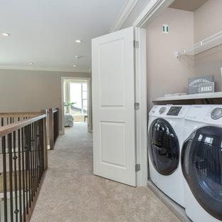 Idee per un ripostiglio-lavanderia design con moquette, lavatrice e asciugatrice affiancate e pavimento beige