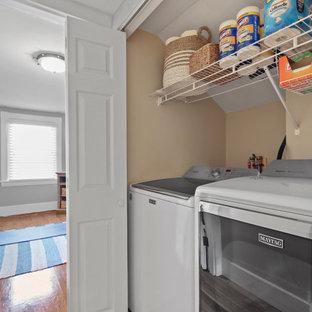 Amerikansk inredning av en liten parallell liten tvättstuga, med öppna hyllor, vita skåp, beige väggar, mellanmörkt trägolv, en tvättmaskin och torktumlare bredvid varandra och beiget golv