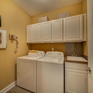 Idéer för att renovera en mellanstor vintage linjär tvättstuga enbart för tvätt, med en nedsänkt diskho, luckor med upphöjd panel, vita skåp, bänkskiva i kvarts, laminatgolv, en tvättmaskin och torktumlare bredvid varandra och bruna väggar