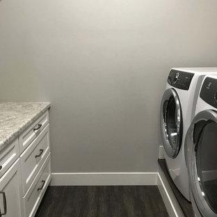 Immagine di una piccola sala lavanderia con ante in stile shaker, ante bianche, top in laminato, pareti grigie, pavimento in vinile, lavatrice e asciugatrice affiancate e pavimento marrone