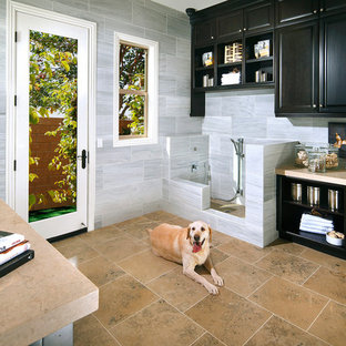 Utility room - huge ceramic floor utility room idea in Orange County with gray walls, a stacked washer/dryer and black cabinets