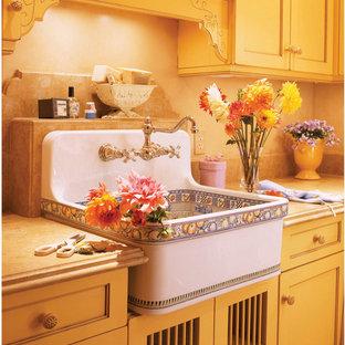 Idee per una lavanderia multiuso mediterranea di medie dimensioni con lavatoio, ante con riquadro incassato, ante gialle, top in granito, pareti beige, pavimento beige, pavimento in gres porcellanato e lavatrice e asciugatrice affiancate