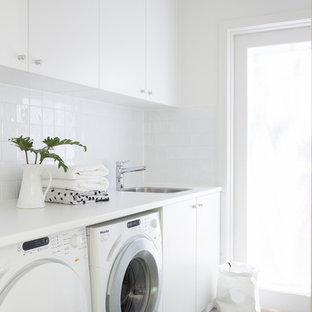 This is an example of a contemporary single-wall dedicated laundry room in Sydney with a drop-in sink, flat-panel cabinets, white cabinets, white walls, a side-by-side washer and dryer, grey floor and white benchtop.
