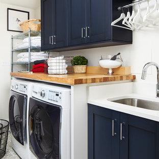 Ejemplo de cuarto de lavado lineal, clásico renovado, con fregadero bajoencimera, armarios estilo shaker, puertas de armario azules, encimera de madera, paredes blancas, lavadora y secadora juntas, suelo gris y encimeras blancas