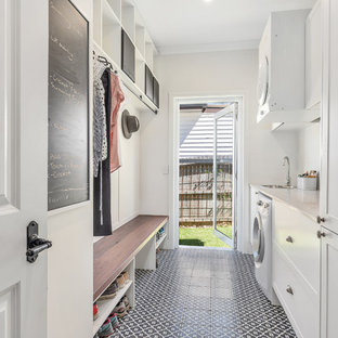 Mid-sized transitional single-wall utility room in Sydney with shaker cabinets, white cabinets, quartz benchtops, white walls, ceramic floors, a stacked washer and dryer, multi-coloured floor, white benchtop and a drop-in sink.