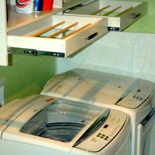 Immagine di una grande sala lavanderia minimal con ante lisce, ante bianche, pareti verdi, pavimento in linoleum e lavatrice e asciugatrice affiancate
