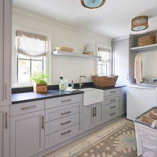Inspiration for a traditional separated utility room in Charlotte with a belfast sink, recessed-panel cabinets, grey cabinets, white walls and black worktops.