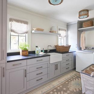 Immagine di una sala lavanderia tradizionale con lavello stile country, ante con riquadro incassato, ante grigie, pareti bianche e top nero