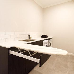 Ispirazione per una sala lavanderia moderna di medie dimensioni con lavello da incasso, ante lisce, ante in legno bruno, top in quarzo composito, pareti bianche, pavimento in gres porcellanato, lavatrice e asciugatrice affiancate, pavimento grigio e top bianco