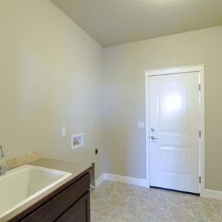Immagine di una sala lavanderia american style con lavatoio, ante in stile shaker, ante in legno bruno, top in laminato, pareti beige, pavimento in linoleum e lavatrice e asciugatrice affiancate