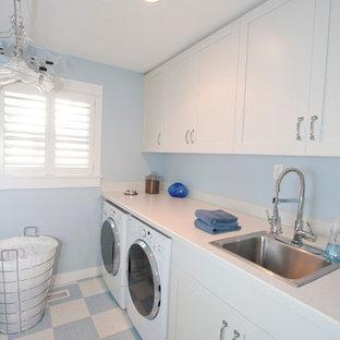 ポートランドの大きいトラディショナルスタイルのおしゃれな洗濯室 (ラミネートカウンター、ドロップインシンク、白いキャビネット、シェーカースタイル扉のキャビネット、青い壁、リノリウムの床、左右配置の洗濯機・乾燥機、マルチカラーの床、白いキッチンカウンター) の写真