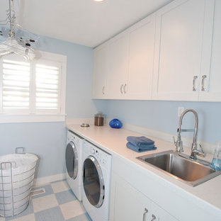 Design ideas for a large classic single-wall separated utility room in Portland with laminate countertops, a built-in sink, white cabinets, shaker cabinets, blue walls, lino flooring, a side by side washer and dryer, multi-coloured floors and white worktops.