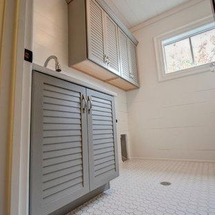 Idee per una sala lavanderia chic di medie dimensioni con lavello sottopiano, ante a persiana, ante grigie, pareti bianche, pavimento con piastrelle in ceramica e lavatrice e asciugatrice affiancate