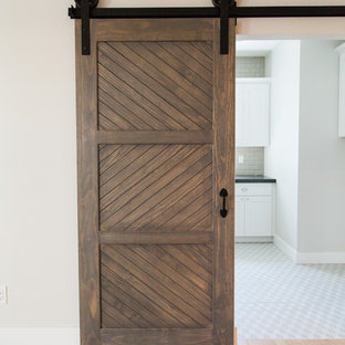 Exempel på en lantlig tvättstuga, med skåp i shakerstil, vita skåp, granitbänkskiva, grå väggar, mellanmörkt trägolv och en tvättmaskin och torktumlare bredvid varandra