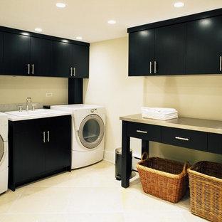 Modern inredning av en tvättstuga, med svarta skåp och beiget golv